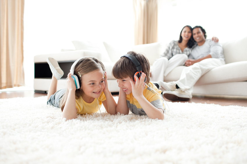 Brother and sister listening music with headphones lying on the floor